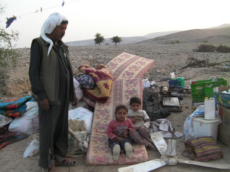 Abu Nahar and two of his daughters with the remains of their home
