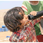 Drinking from a portable water tank in Al Hadidiya